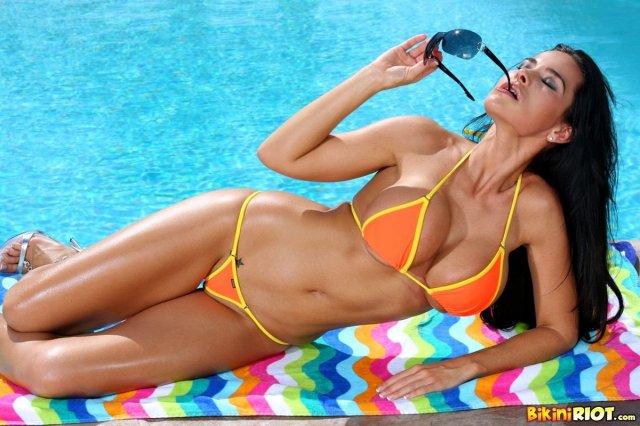 Сексуальная девушка Playboy с большими сиськами позирует в мини бикини.