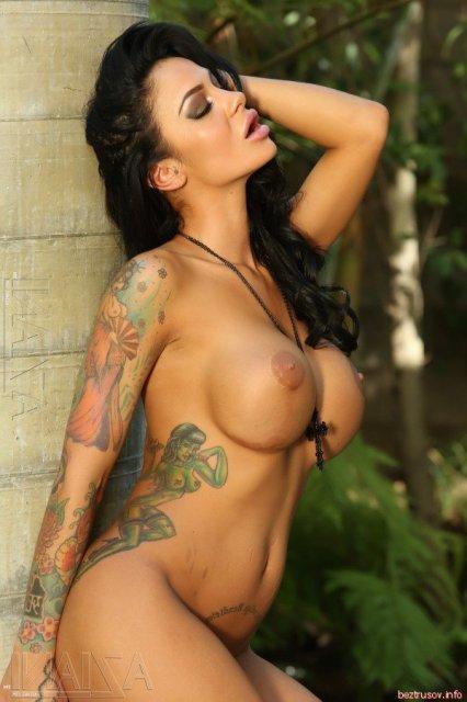 Татуированная красотка позирует и трахает себя вибратором.