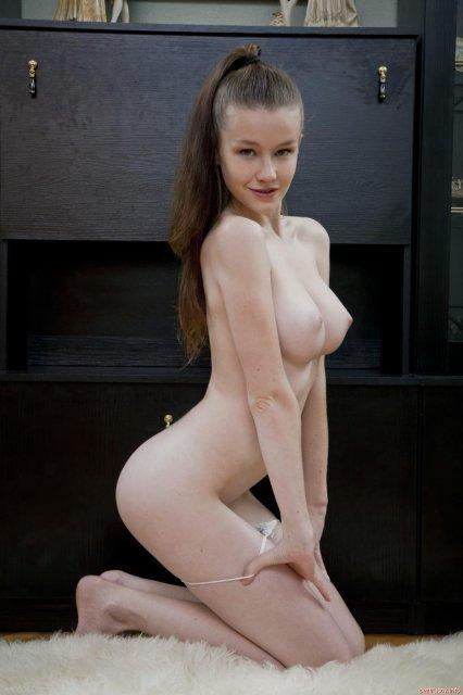 Молодая сексуальная девчонка позирует голая, показывая сиськи