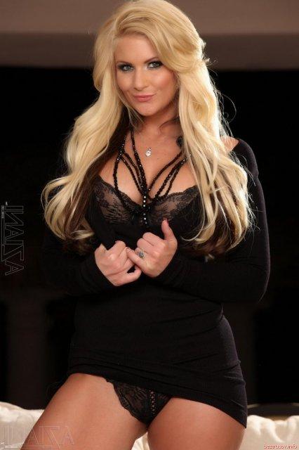 Длинноволосая блондинка эротично позирует в сексуальном белье.
