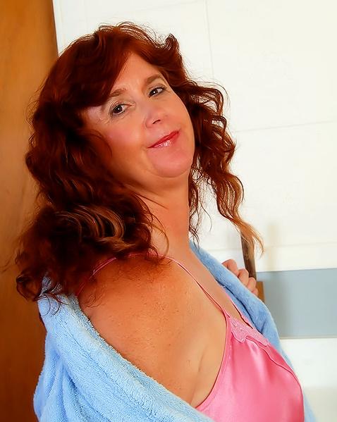 Зрелая рыжая женщина мастурбирует лохматую пизду демонстрируя жопу