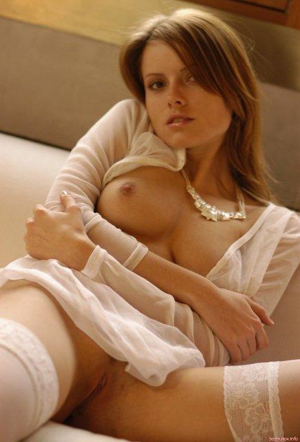 Богатая дева в чулках обнажённой на кровати ласкает киску с гладким лобком