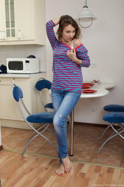 Молодая домохозяйка снимает стринги на кухне, показывая волосатую пилотку