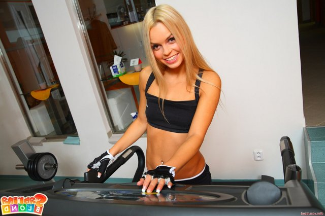 Гимнастка с красивой грудью ласкает половые губы в спортзале