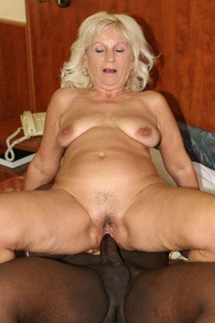 Старая женщина с волосатым лобком дрочит черный хуй между грудей