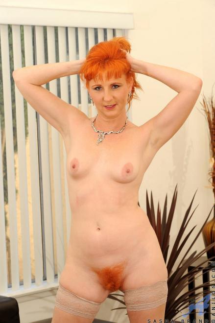 Зрелая рыжая женщина мастурбирует фаллоимитатором и трахается в волосатую писю