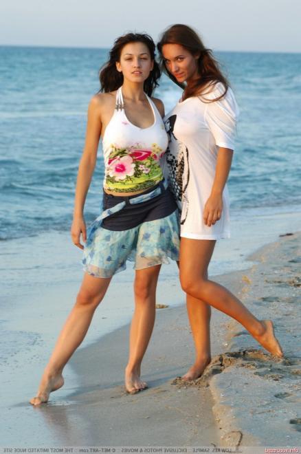 Подруги нудистки на пляже позируют голыми и ласкаются