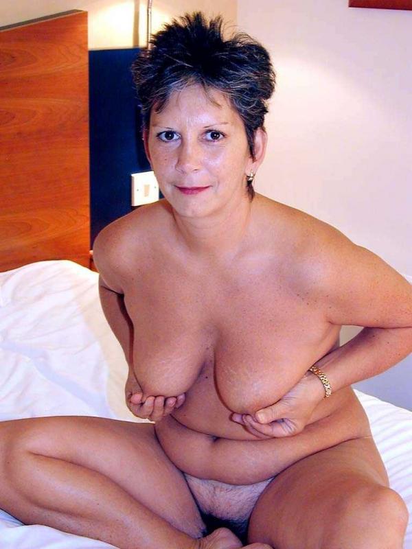 Настоящая бабка голою позирует на кровати, показываю волосатую мотню