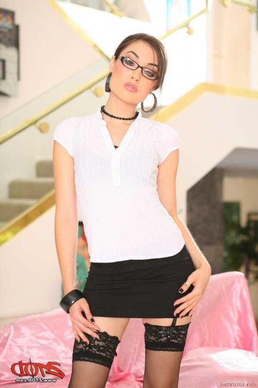 Эротичное позирование Саши Грей в очках и костюме училки
